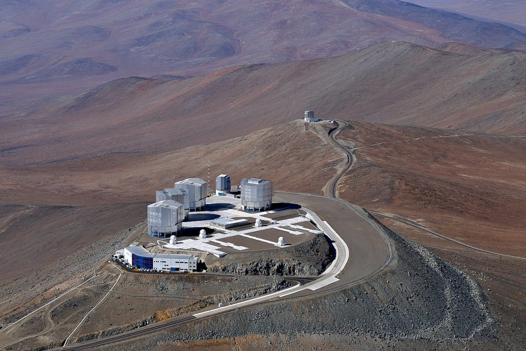 A bird soaring over the remote, sparsely populated Atacama Desert in northern Chile — possibly the driest desert in the world — might be surprised to come upon the technological oasis of ESO's Very Large Telescope (VLT) at Paranal. The world's most advanced ground-based facility for astronomy, the site hosts four 8.2-metre Unit Telescopes, four 1.8-metre Auxiliary Telescopes, the VLT Survey Telescope (VST), and the 4.1-metre Visible and Infrared Survey Telescope for Astronomy (VISTA), seen in the distance on the next mountain peak over from the main platform. This aerial view also shows other structures, including the Observatory Control Room building, on the main platform's front edge.