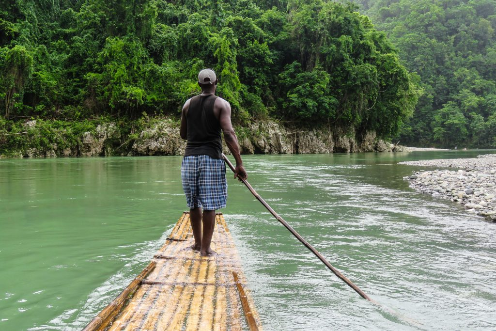 Bamboo raft navigates the Rio Grande river in Jamaica for the ultimate rafting experience as one of the things to do in montego bay