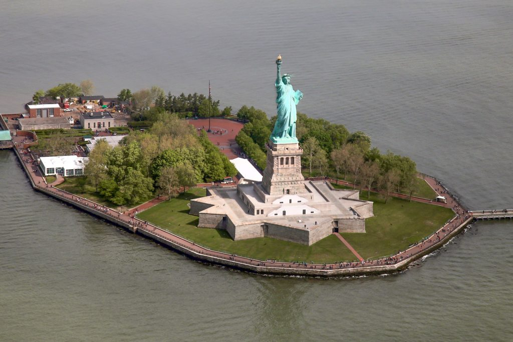 Statue of Liberty from above. NYC helicopter tours give views acros the New York City skyline. One of the best things to do in NYC and on the new york itinerary. Flight seeing Statue of Liberty, Manhattan helicopter tours, hudson, chelsea, empire state building, central park, brooklyn bridge. One of many things to do in new york.
