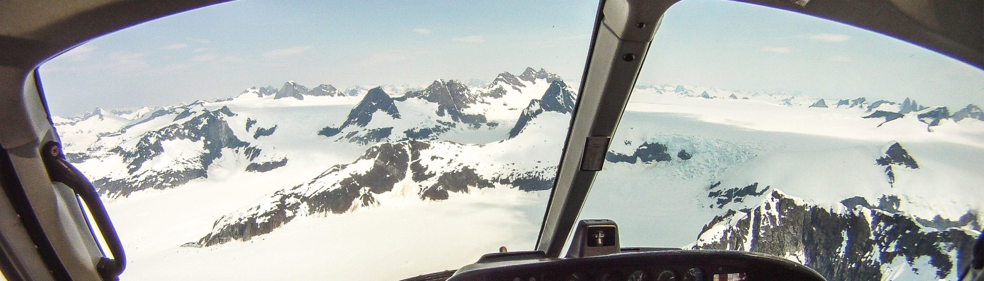Helicopter flight to the Juneau Icefield for trekking on the Mendenhall Glacier from an Alaska cruise and Inside Passage. Helicopter cockpit from GoPro Cmaera