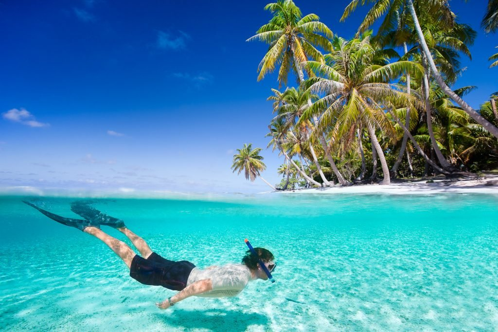 Maldives Resorts snorkelling beach. Man swimming in a clear tropical waters in front of exotic island