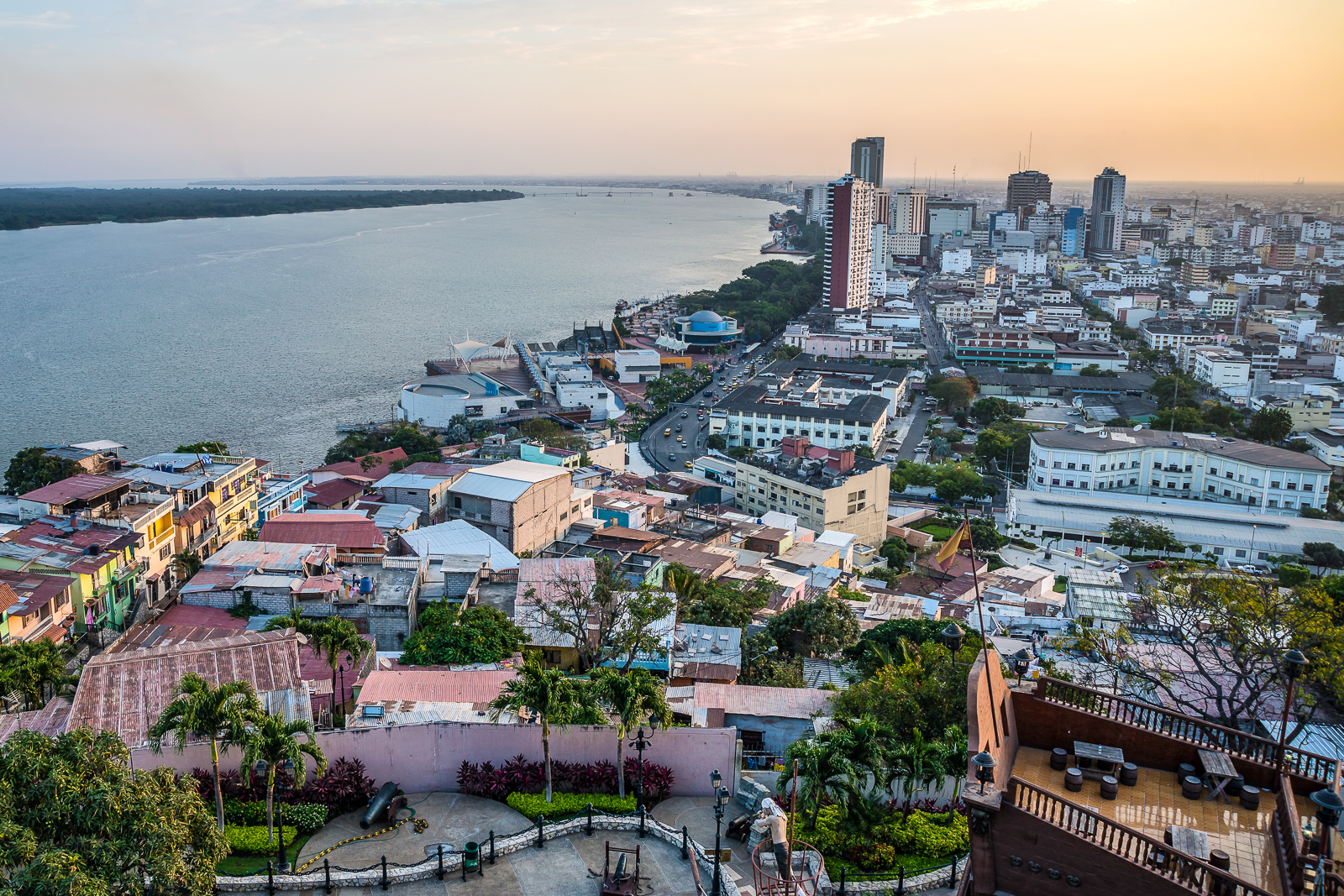 Things to do in Ecuador: High view of the city of Guayaquil and it's river, at sunset. One of the top places to visit in Ecuador. It is easy to fluinto Guayaquil airport from Quito or other international destinations. Guayaquil airport is a gateway to the Galapagos Islands Ecuador.