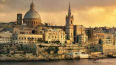 Things to do in Malta travel tips europe on a budget. Panoramic view of Valletta at sunset with Carmelite Church dome and St. Pauls Anglican Cathedral. Malta