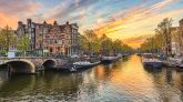 Places to visit in Amsterdam, discover all the top things to do in Amsterdam. Amsterdam sunset city skyline at canal waterfront, Amsterdam, Netherlands