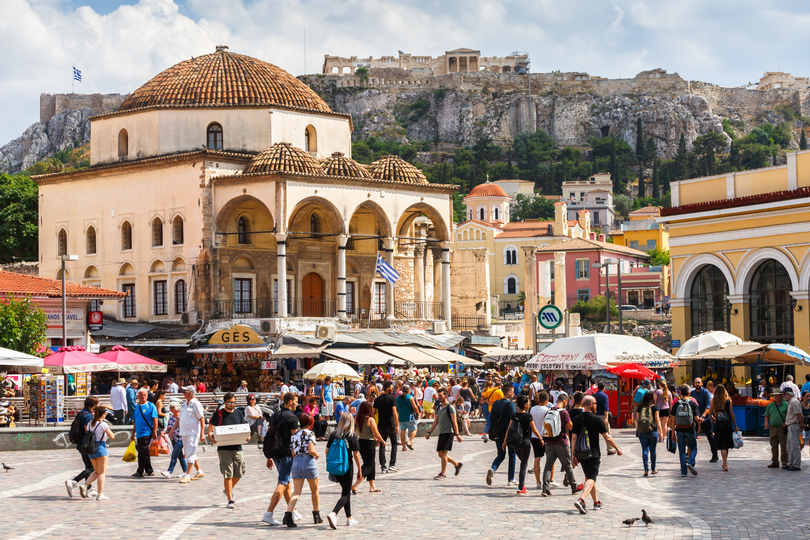 "Things to see in Athens Plaka Athens, Greece - May 25, 2018: People in Monastiraki square and view of Acropolis and the old mosque in the centre of Athens, Greece. ""n"