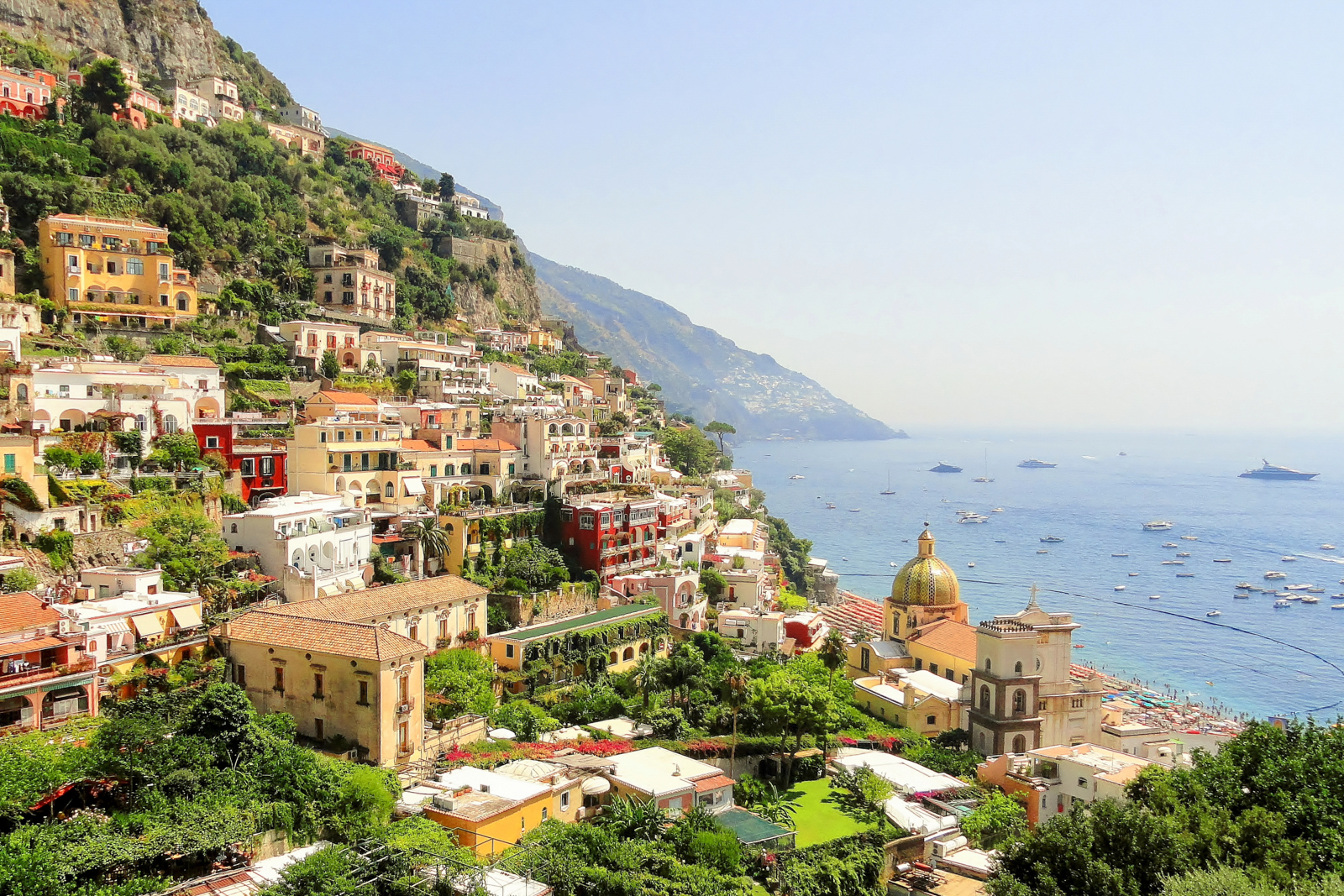 Top things to do in Amalfi Coast attractions like A view from the hill at colorful Positano town with the church and sea.