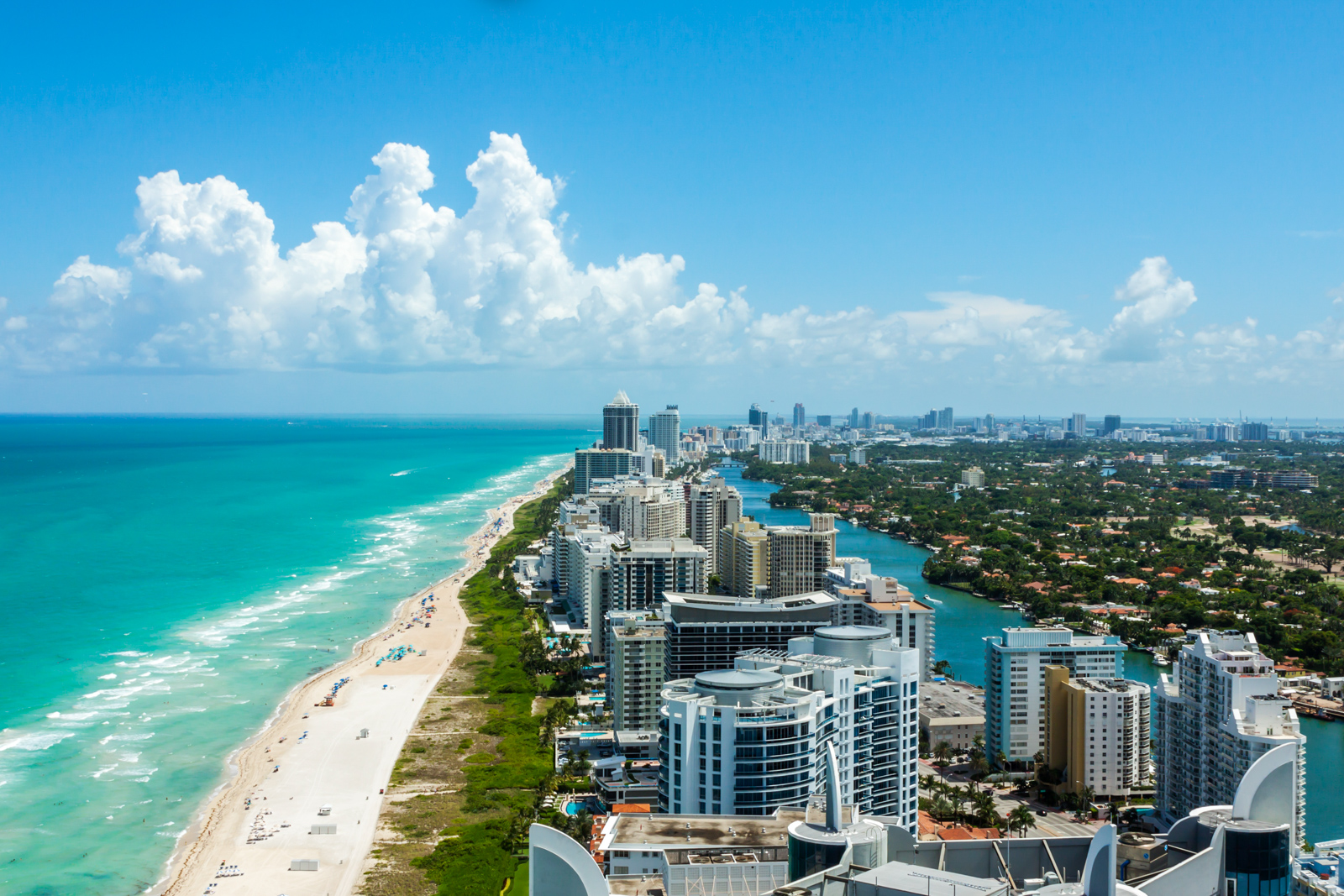 Looking down South Beach in Miami. Full view of the beach on the left and the city on the right. Beautiful blue sky on a clear day. Your guide for all the top Miami attractions and best things to do in Miami. There are Plenty of tourist attractions in Miami Florida. This Guide presented by Flying and Travel.