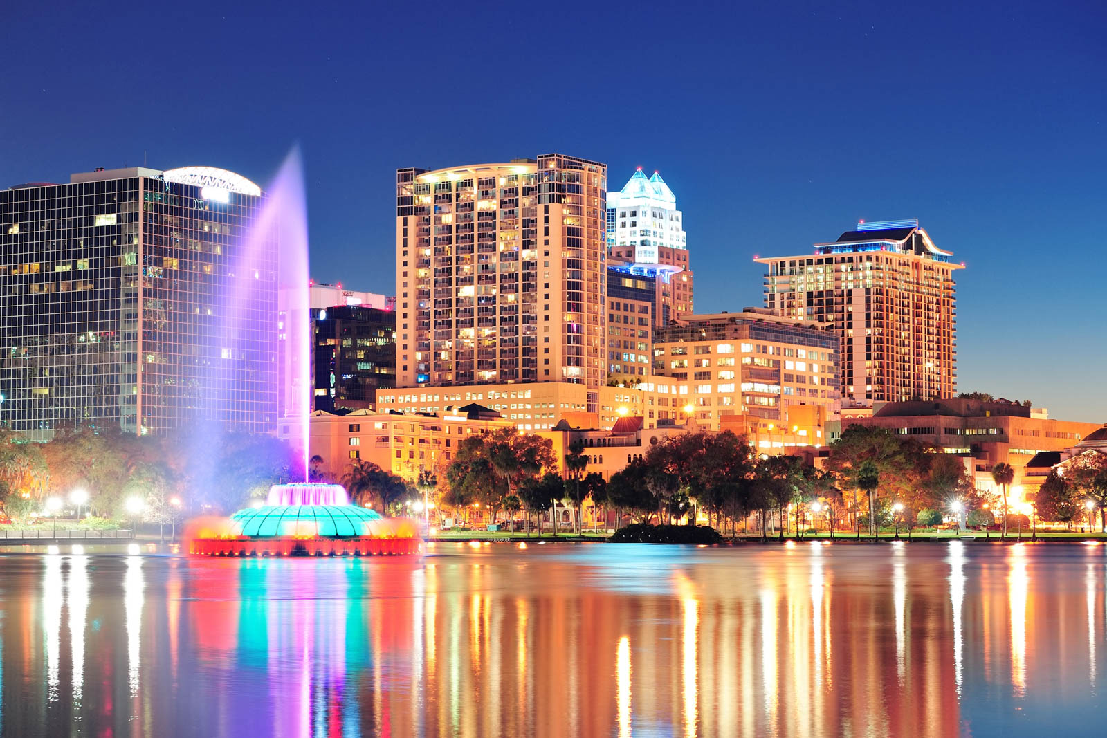 Orlando downtown skyline panorama over Lake Eola. The nightlife in the city is one of the best things to do in Orlando for Adults and activities on Lake Eola are unique things to do in Orlando.